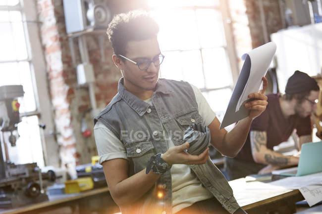 Jeune designer examinant prototype et notes en atelier — Photo de stock