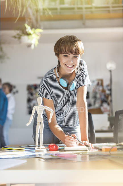 Portrait smiling female design professional with artist?s figure sketching in office — Stock Photo