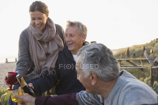 Смеющийся старший пары пить шампанское на пляж заката. — стоковое фото