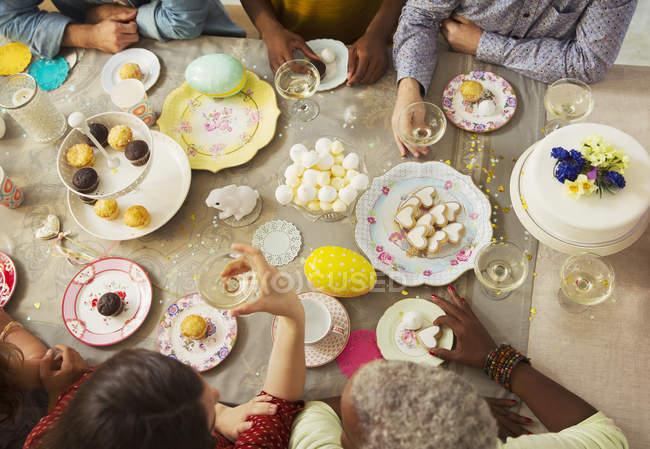 Вид зверху сім'ї насолоджуючись Великдень десерти і п'є шампанське столом — стокове фото