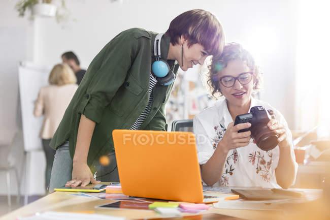 Profesionales del diseño de fotógrafos con cámara SLR en el portátil - foto de stock