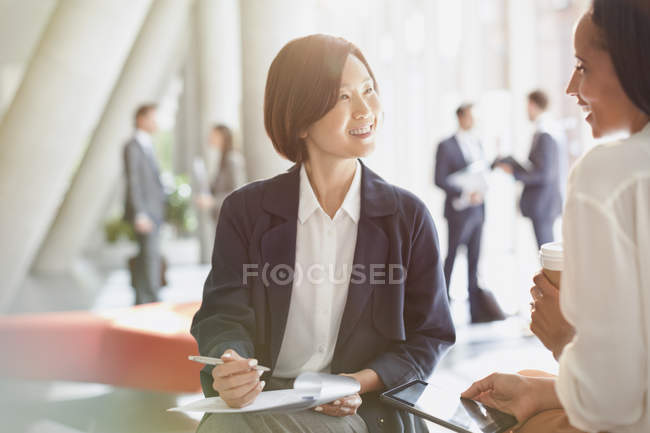 Smiling businesswomen meeting reviewing paperwork in office lobby — Stock Photo