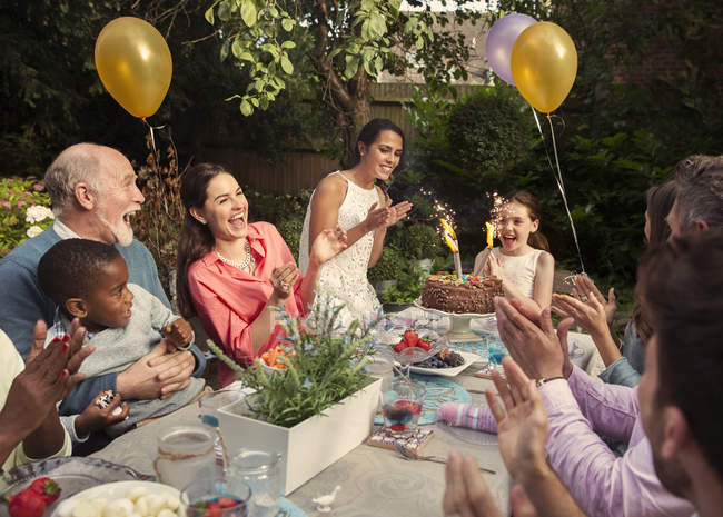 Multi-ethnic multi-generation family clapping celebrating birthday with fireworks cake at patio table — Stock Photo
