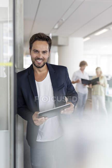 Portrait smiling businessman holding digital tablet in office — Stock Photo