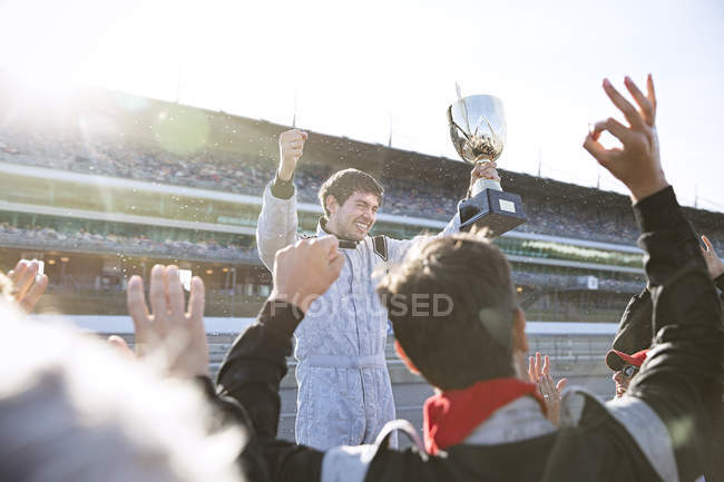 Formula one racing team cheering for driver with trophy, celebrating victory on sports track — Stock Photo
