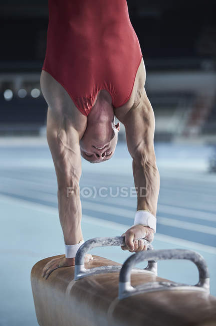 Мужчина гимнаст, выступающий с перевернутой ладонью на коне — стоковое фото