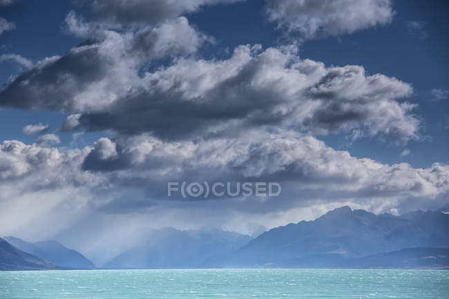 Fluffy clouds above tranquil blue Lake Pukaki, South Island, New Zealand — Stock Photo