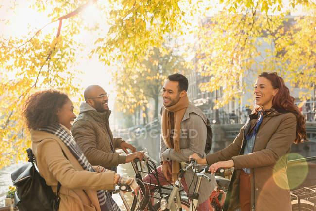 Sorridente giovane coppia amici con biciclette parlando sotto l'albero di autunno soleggiato — Foto stock