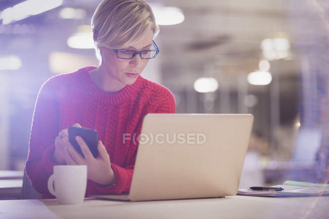 Serious businesswoman working late, using cell phone at laptop in office — Stock Photo