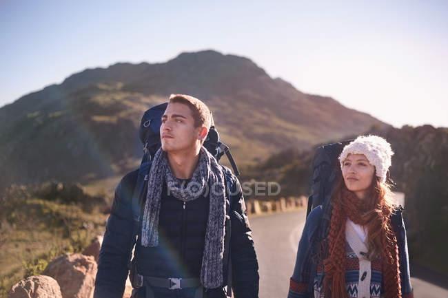 Молоді пара з рюкзаками походи на віддалених, Сонячний дорозі — стокове фото