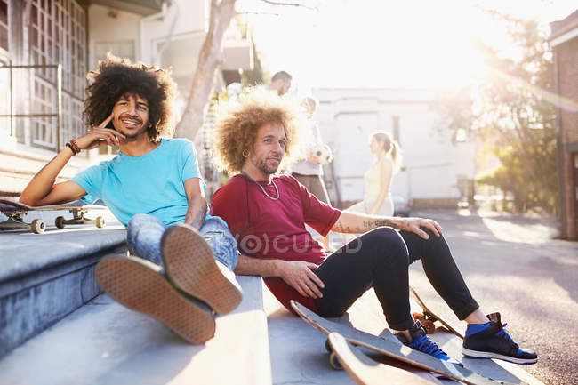 Portrait confident male friends with skateboards hanging out on sunny urban steps — Stock Photo