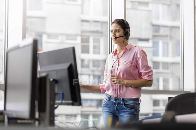 Businesswoman talking on telephone using hands-free device in office — Stock Photo