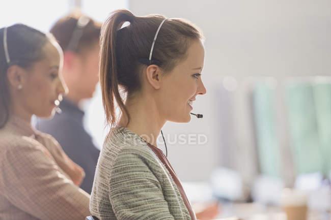 Улыбающаяся женщина-телемаркетер в наушниках разговаривает по телефону в офисе — стоковое фото