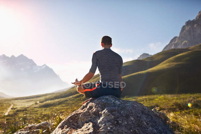 Young man meditating on rock in sunny, remote valley — Stock Photo