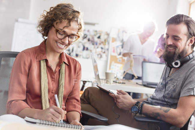 Smiling design professionals meeting and sketching in office — Stock Photo