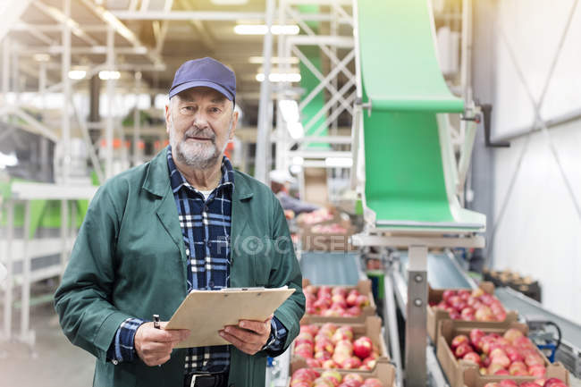 Portrait confident manager with clipboard in apple food processing plant — Stock Photo