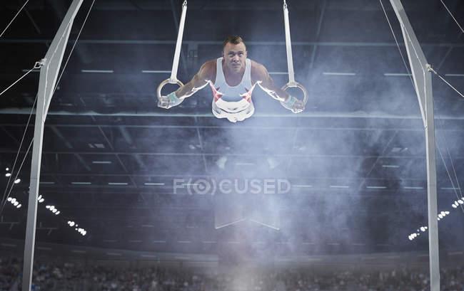 Männerturner turnen in der Arena an den Ringen — Stockfoto