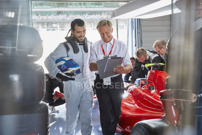 Manager and formula one race car driver talking in repair garage — Stock Photo