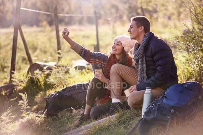 Молода пара, взявши перерву в походи, беручи selfie з камерою телефону — стокове фото