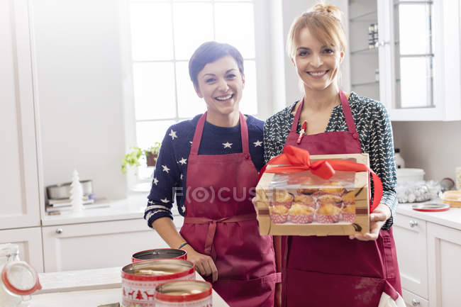 Portrait de traiteuses souriantes montrant boîte enveloppée de pâtisseries dans la cuisine — Photo de stock