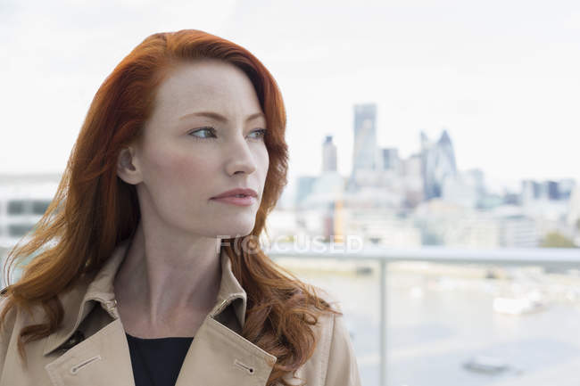 Portrait pensive businesswoman with red hair looking away on urban balcony — Stock Photo