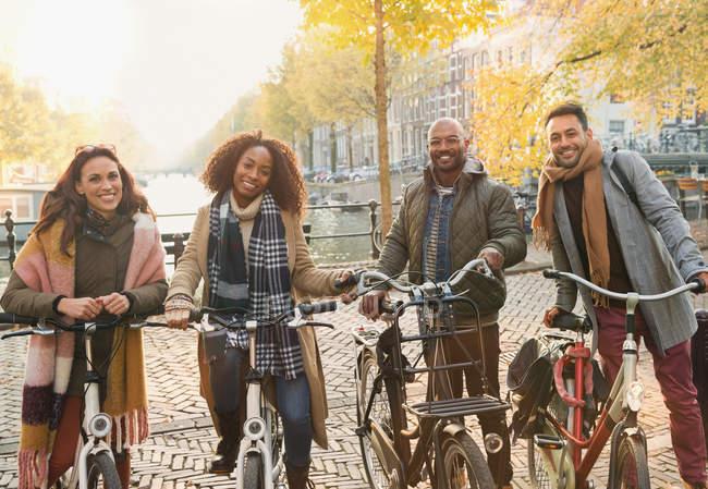 Портрет улыбающихся друзей езда на велосипеде на городской осенней улице, Амстердам — стоковое фото