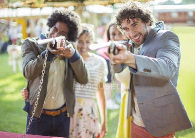 Молодые люди с оружием в парке аттракционов — стоковое фото