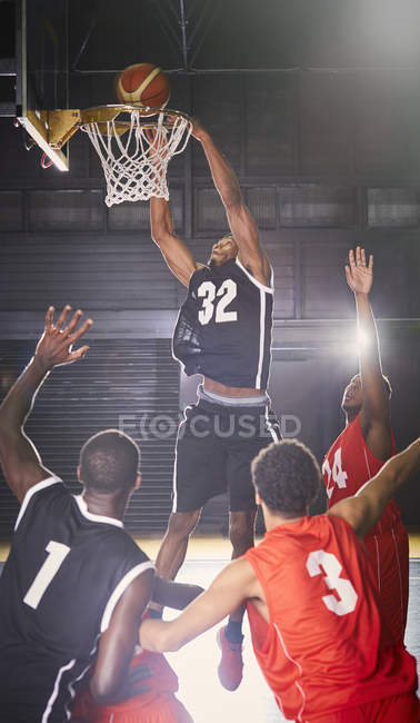 Giocatore di pallacanestro maschio giovane inzuppare la palla in cerchio con i difensori qui sotto — Foto stock
