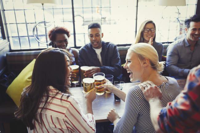 Amigos rindo brindando copos de cerveja na mesa no bar — Fotografia de Stock