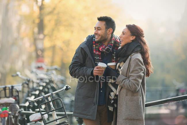 Souriant jeune couple en vêtements chauds boire du café en ville — Photo de stock