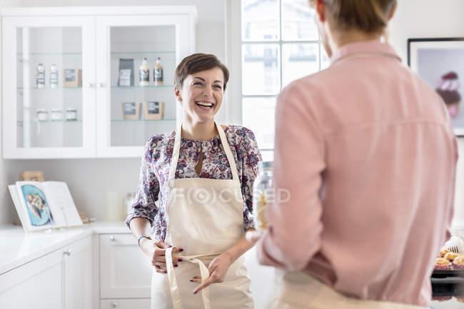 Traiteuses souriantes attachant des tabliers dans la cuisine — Photo de stock