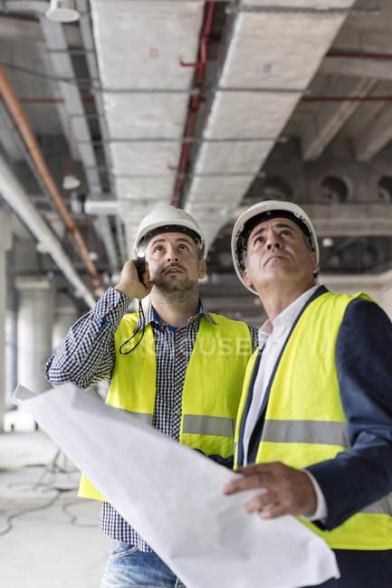 Инженеры-мужчины с фонариком и чертежами, смотрящие вверх на строительной площадке — стоковое фото