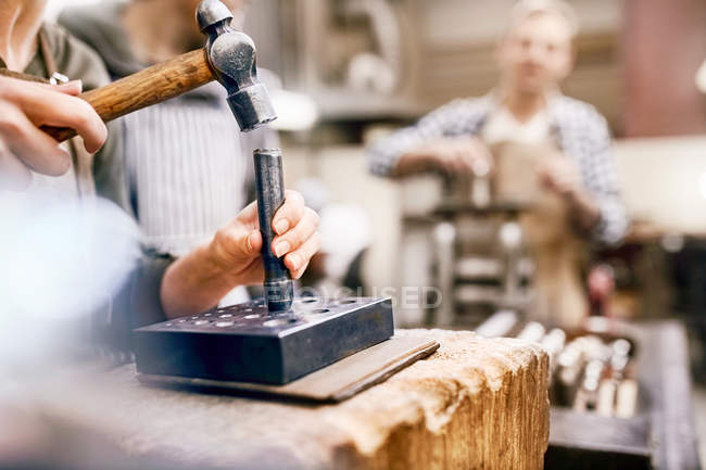 Jeweler using hammer and equipment in workshop — Stock Photo