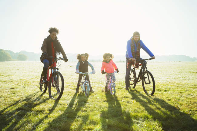 Portrait young family bike riding in sunny autumn park grass — Stock Photo