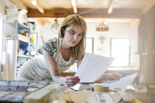 Stained glass artist examining drawings in studio — Stock Photo