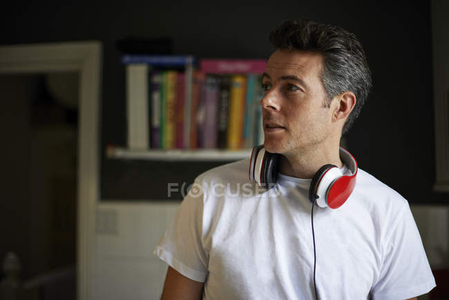 Man at home with red headphones over his neck looking away — Stock Photo
