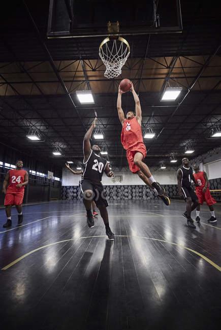 Молодой баскетболист прыгает на слэм-данк баскетбол в игре на корте в гимназии — стоковое фото