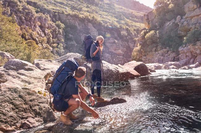 Giovani coppie con Zaini escursionismo, spruzzi d'acqua a flusso — Foto stock