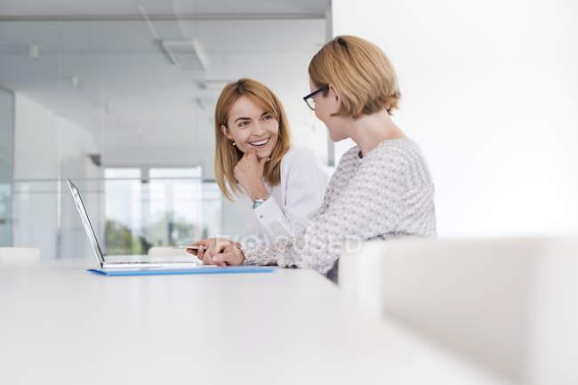 Бізнес-леді працюють на ноутбук, у конференц-залі — стокове фото