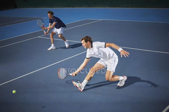 Молодые теннисисты в парном разряде играют в теннис, доставая теннисную ракетку на синем теннисном корте — стоковое фото
