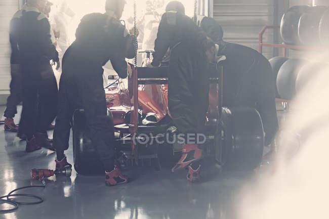 Tripulação de poço trabalhando na fórmula um carro de corrida na garagem de reparação — Fotografia de Stock