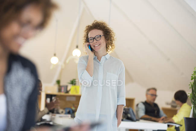 Portrait of woman talking on phone in modern office — Stock Photo