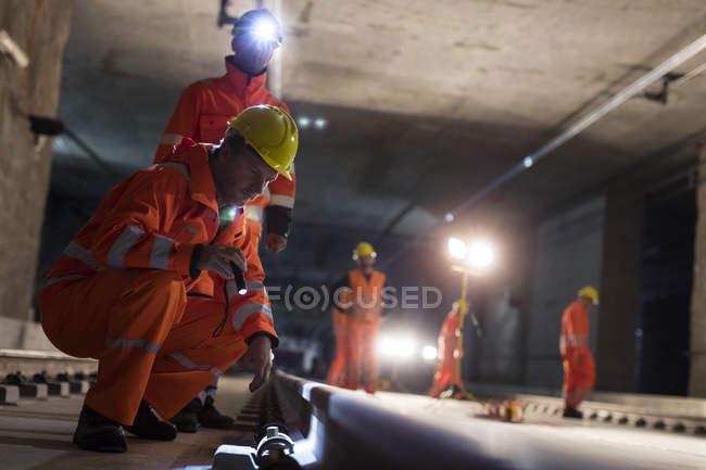 Trabalhadores da construção masculina examinando pistas subterrâneas no local de construção subterrâneo escuro — Fotografia de Stock