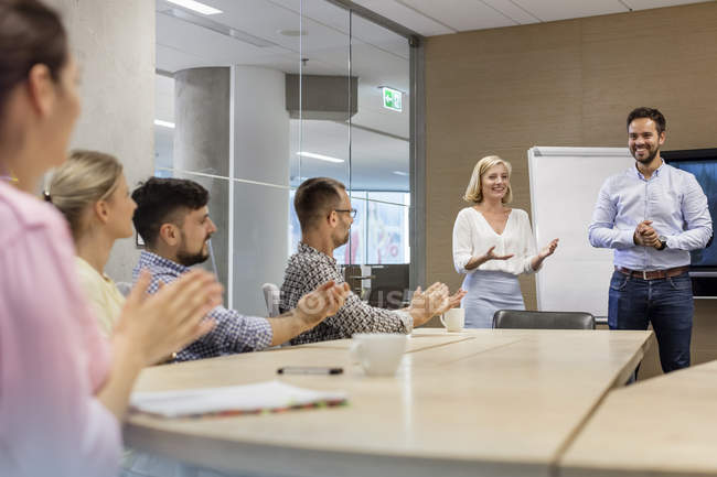 Business people clapping for businessman in conference room meeting — Stock Photo