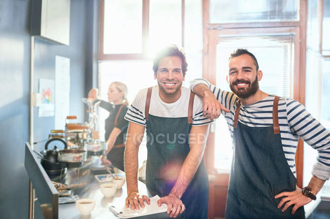 Portrait smiling, confident male coffee roasters tasting coffee — Stock Photo