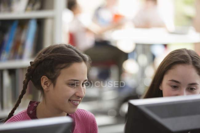 Filles recherchant, à l'aide d'ordinateur dans la bibliothèque — Photo de stock