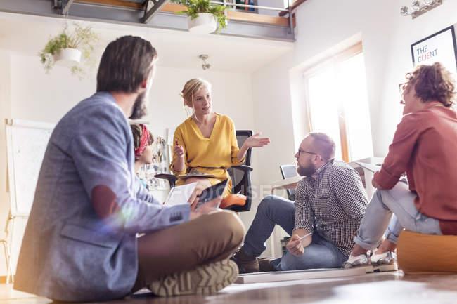 Встреча дизайнеров, сидящих на полу — стоковое фото
