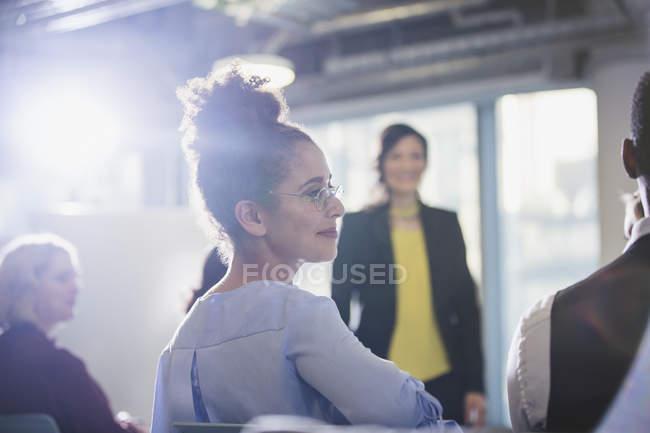 Femme d'affaires tournant, à l'écoute dans l'auditoire de la Conférence — Photo de stock