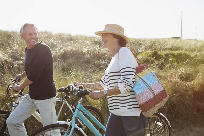 Couple d'âge mûr vélo de marche sur la plage ensoleillée herbe chemin — Photo de stock