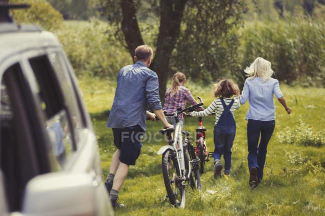 Famiglia a piedi mountain bike lontano dalla macchina — Foto stock